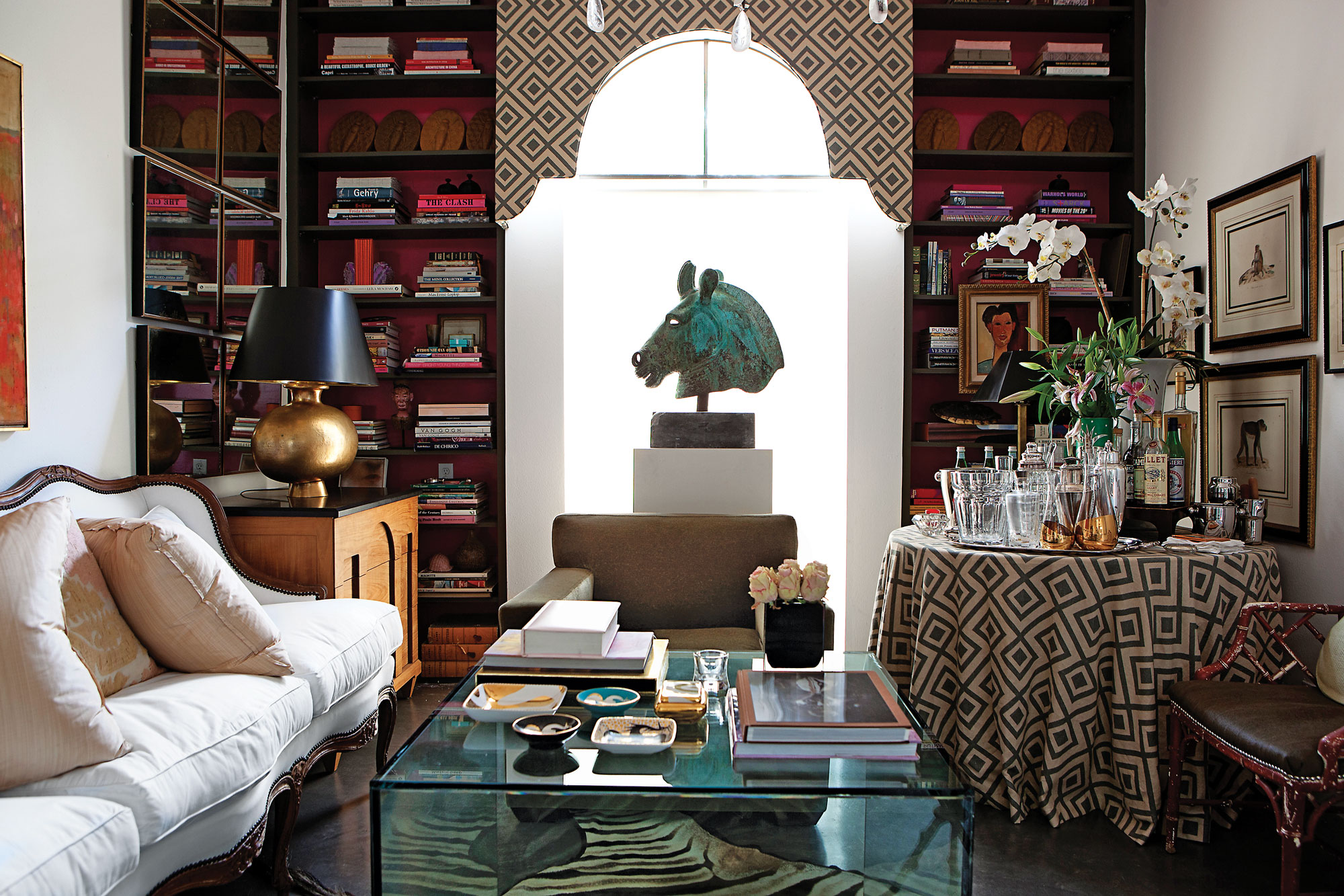 The library/den is centered around a Roman bronze horse head from Biff Agee, which sits atop a custom wooden stand. Valence is covered in David Hicks La Florentina from Lee Jofa\Kravet, flanked by a pair of bookshelves painted olive with hot-pink interior. A David Hicks-inspired drinks table holds a large silver tray, Baccarat ice bucket, collection of vintage crystal shakers and decanters. Antique hand colored prints were gifts from Cathy's mother. Faux-bamboo chair covered in olive-colored cowhide. Zebra rug from Custom Creations is beneath a custom glass cube coffee table. An 18th-century French Louis XIV sofa from James Powell is flanked by Donghia chests and Robert Kuo hammered-gold, washed-bronze lamps from Ellouise Abbott.