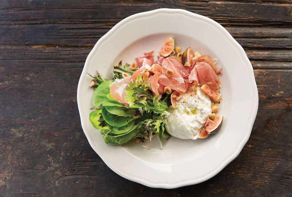 Relish's fig salad features burrata, sliced proscuitto, toasted hazelnuts, watercress, and a lemon, maple vinaigrette.