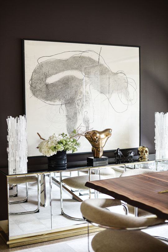 In the dining room, Nadara Goodwin's Sea Mouth with Hook hovers above a vintage Mastercraft mirrored console from Give and Take. Two vintage Cleo Renault Lucite column lamps flank a bronze sculpture by Nigel Richie from the family collection of Clair's husband, David.