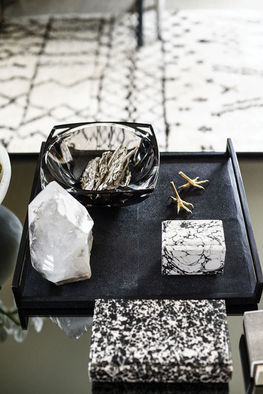 Mixed materials work magic on the custom smoked-mirror cube coffee table: R+Y Augousti shagreen tray and boxes, Baccarat bowl, gold crow's-feet sculptures from D.L. & Co. and a crystal found at an estate sale.