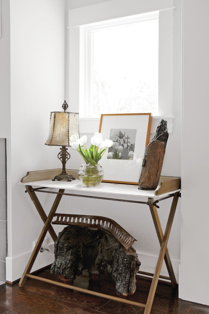 "In one nook in the living room, a wood-and-marble table grounds a beautiful vignette. Vintage print by Trudi Blom, gifted to Cusack by her mom, Barbara Hill; the image records people of the vanishing Lacandon Rain Forest, Chiapas. Underneath, one of Cusack's sculptures features charred wood from her ""Campfire Stories,"" exhibited at Koelsch Gallery, 2009."