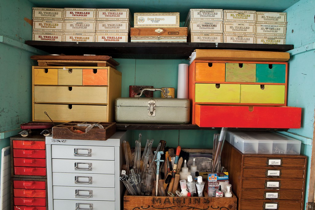 Tools, drawers and her dad's cigar boxes line a work cabinet.