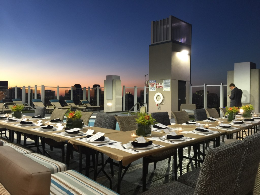 A beautiful sunset bathes the FEED Supper tablescape at Skyhouse River Oaks.