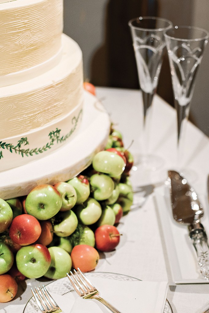 The wedding cake made by Who Made the Cake sat on a plate of miniature apples.