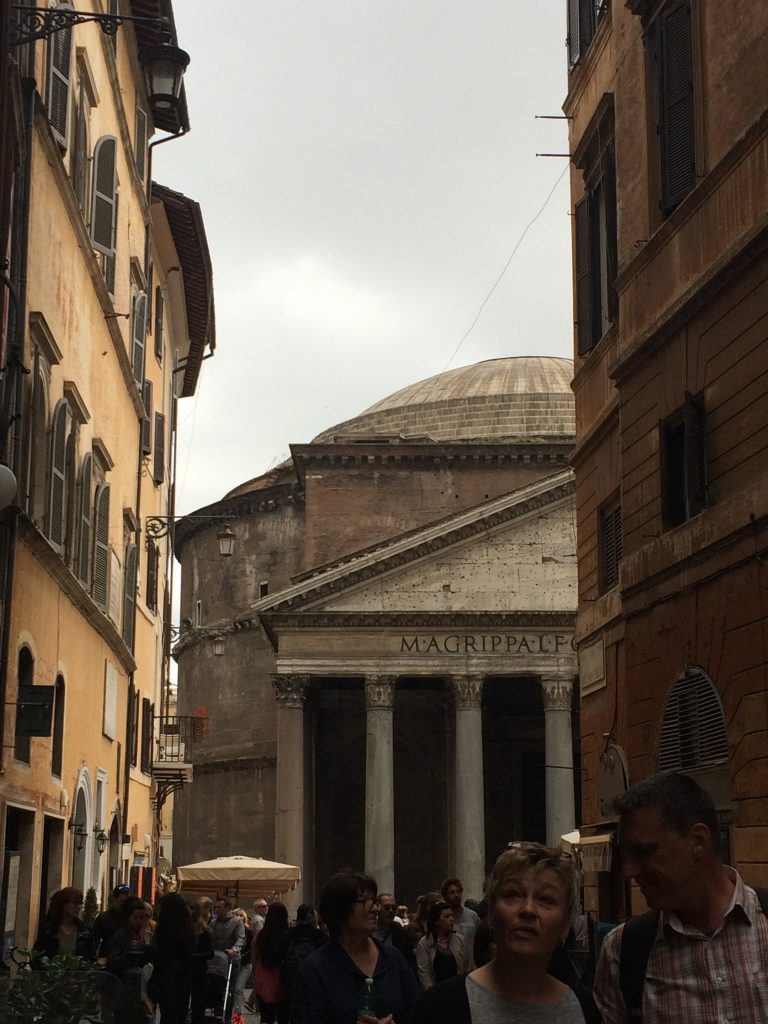 The Pantheon emerges at the end of the street.