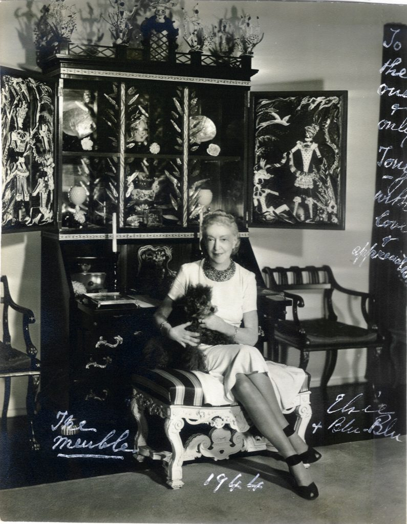 Elsie de Wolfe with Blu-Blu in front of her meuble designed by Tony Duquette, 1942