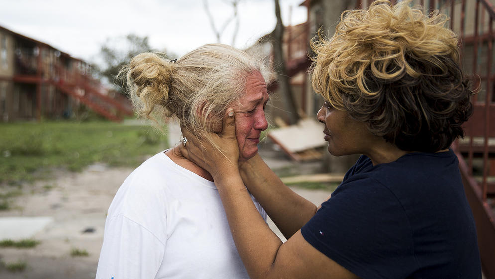 Lifelong friends comfort each other in Refugio, Texas. (Photo by Nick Wagner / Austin American-Statesman via AP)